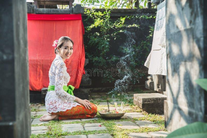 Mujer del Balinese que sonríe después de rogar en el templo en pequeñas capillas fotografía de archivo