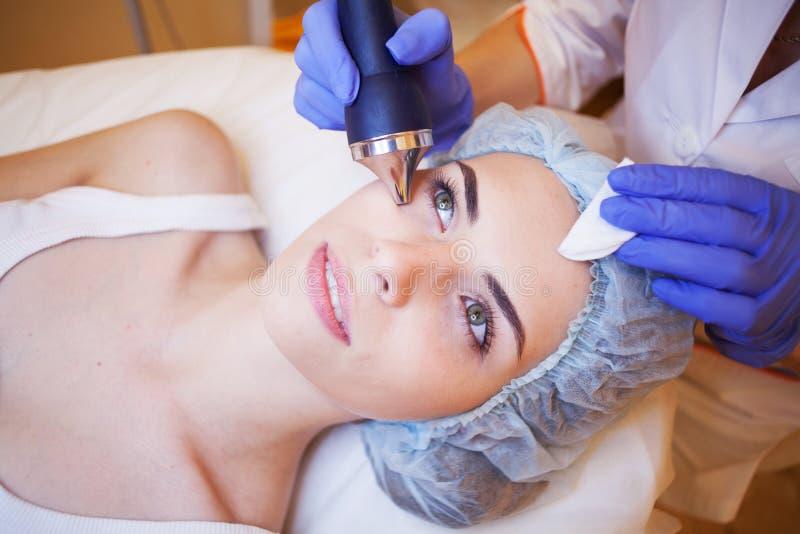 Mujer del balneario de la cosmetología que hace procedimientos en la cara foto de archivo libre de regalías