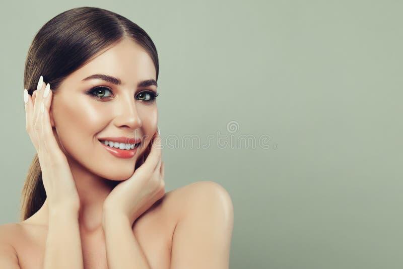 Mujer del balneario que sonríe y que toca su mano su cara fotografía de archivo