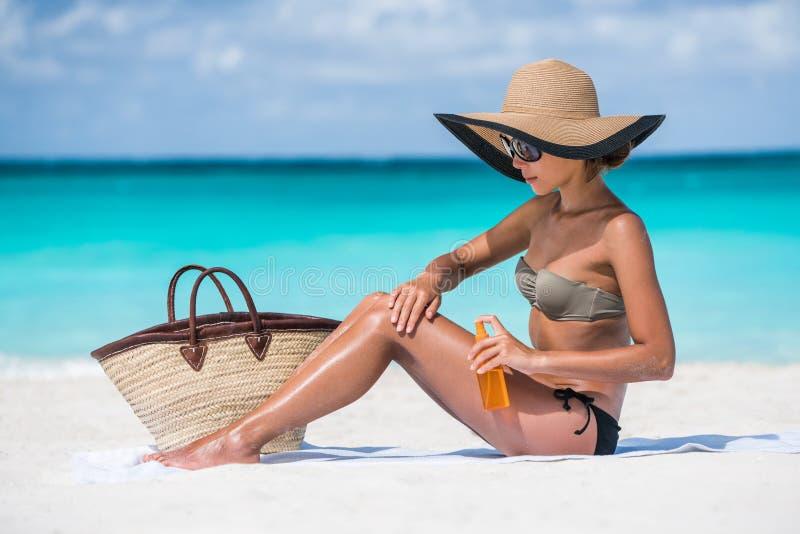 Mujer del bikini del esencial de la playa que pone la protección solar fotos de archivo