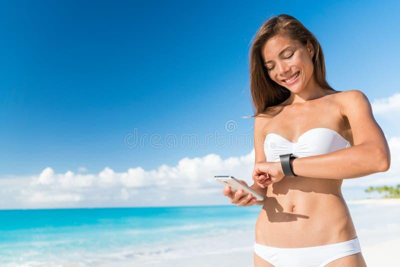 Mujer del bikini que usa datos syncing del reloj del teléfono elegante foto de archivo libre de regalías