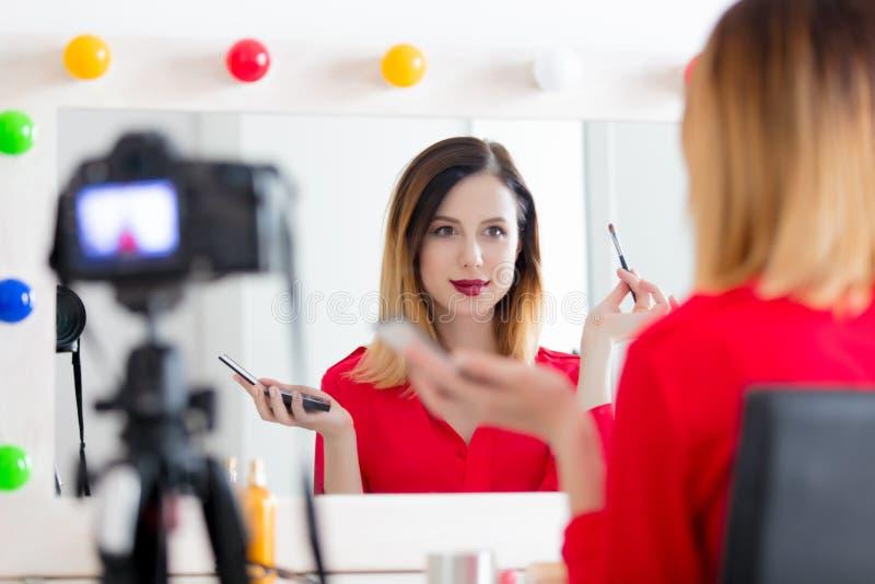 Mujer del Blogger que aplica los cosméticos en la cámara imagen de archivo libre de regalías
