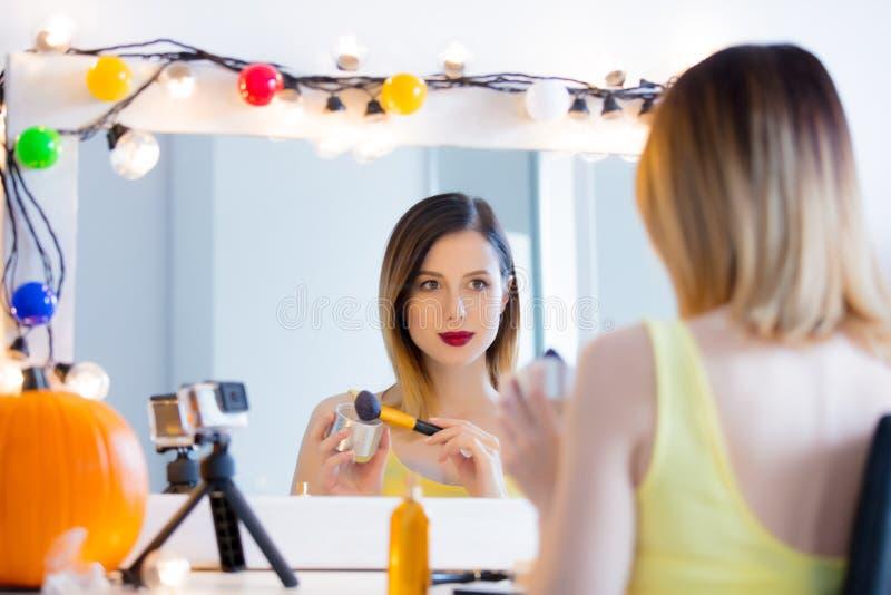 Mujer del Blogger que aplica los cosméticos en la cámara imágenes de archivo libres de regalías