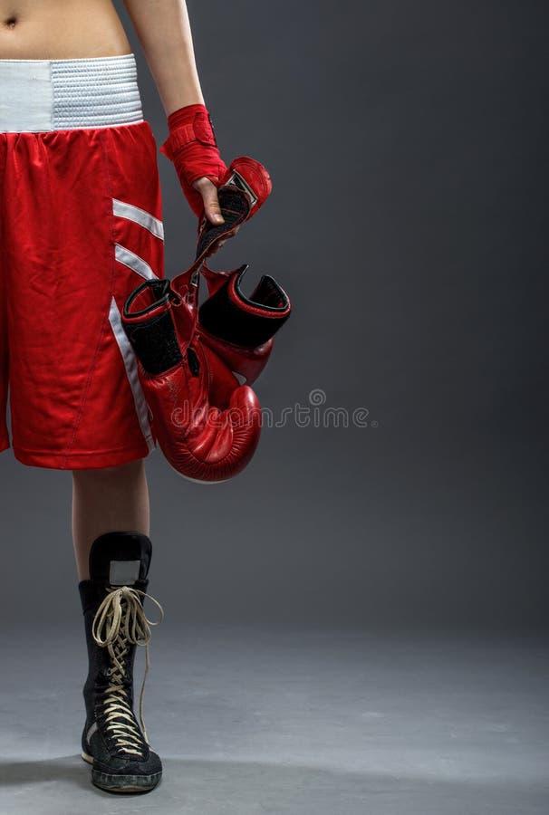 Mujer del boxeo que se coloca en el vestido de la caja, sosteniendo los guantes de boxeo - media foto del cuerpo imagen de archivo