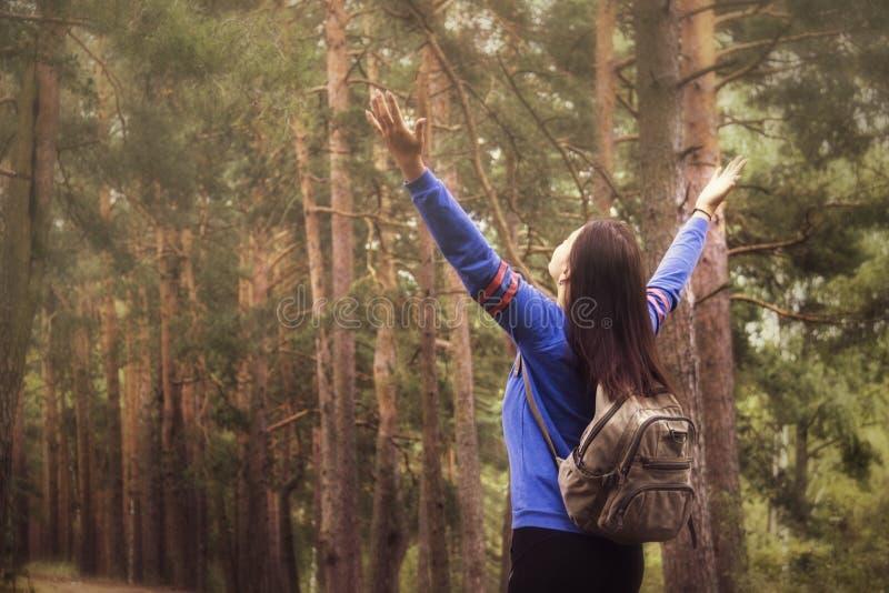 Mujer del caminante con los brazos aumentados para arriba en la naturaleza al aire libre, visión trasera imágenes de archivo libres de regalías