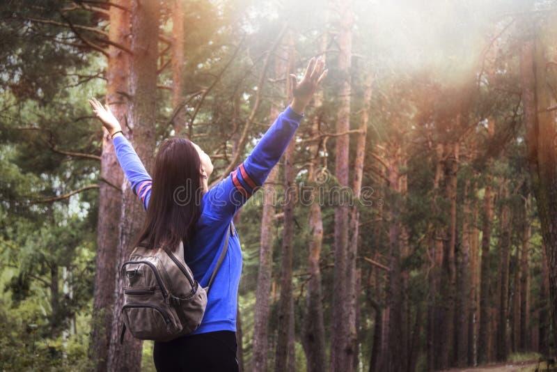 Mujer del caminante con los brazos aumentados para arriba en la naturaleza al aire libre, visión trasera foto de archivo libre de regalías