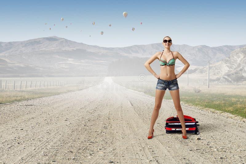 Mujer del caminante de tirón en el camino fotos de archivo