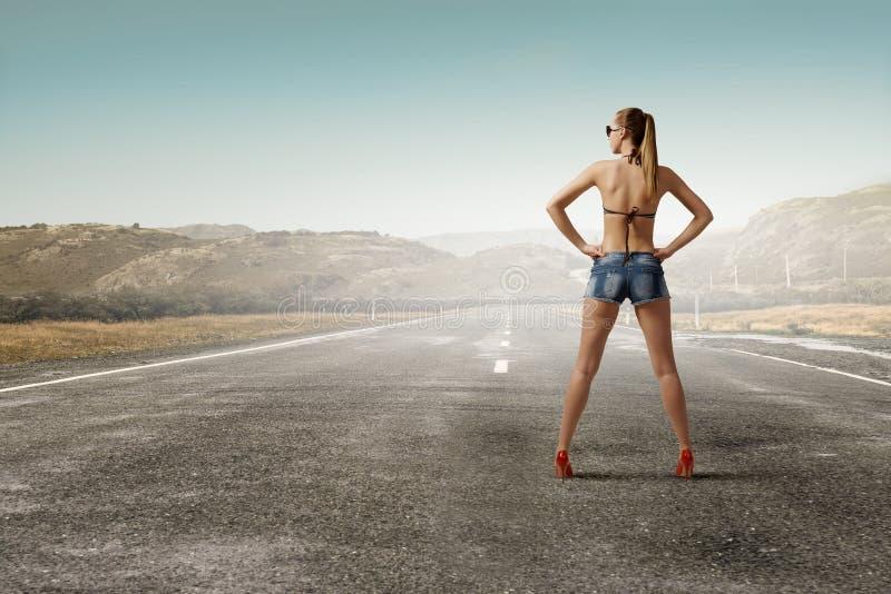 Mujer del caminante de tirón en el camino fotografía de archivo libre de regalías