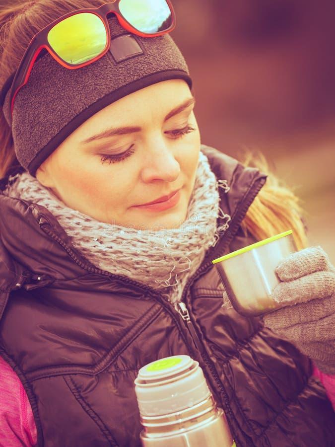 Mujer del caminante que calienta té de la bebida en día frío fotos de archivo libres de regalías