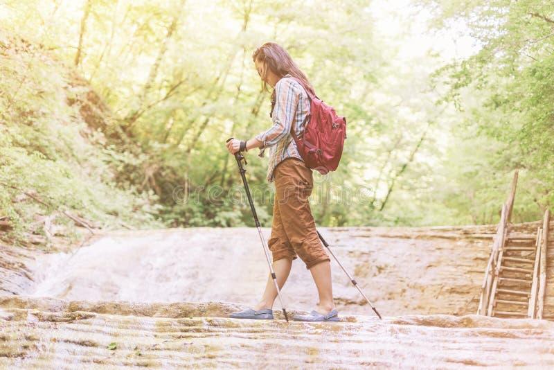 Mujer del caminante que cruza un río con emigrar polos fotos de archivo