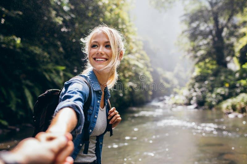 Mujer del caminante que lleva a cabo la mano del hombre en un alza de naturaleza fotografía de archivo libre de regalías