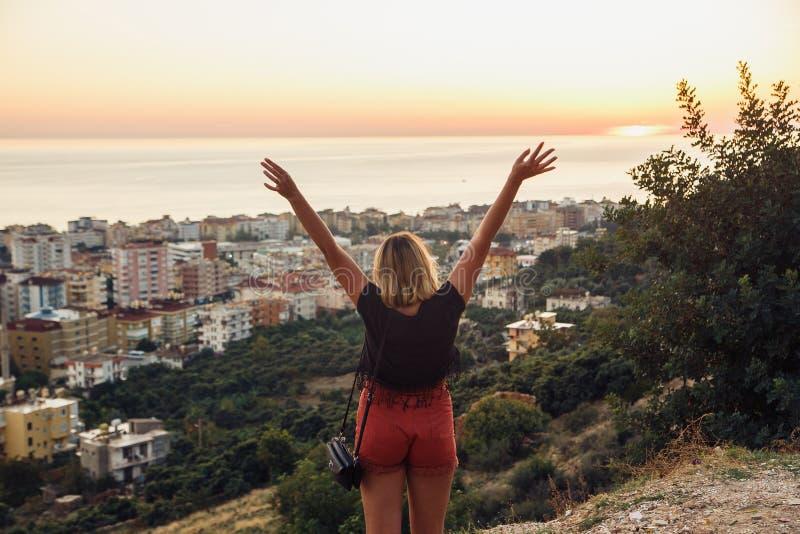 Mujer del caminante que se coloca con las manos para arriba que alcanzan el top La muchacha acoge con satisfacción una puesta del fotos de archivo