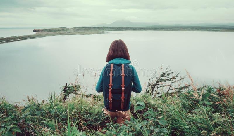 Mujer del caminante que se coloca en la colina y el goce de la opinión del lago imágenes de archivo libres de regalías