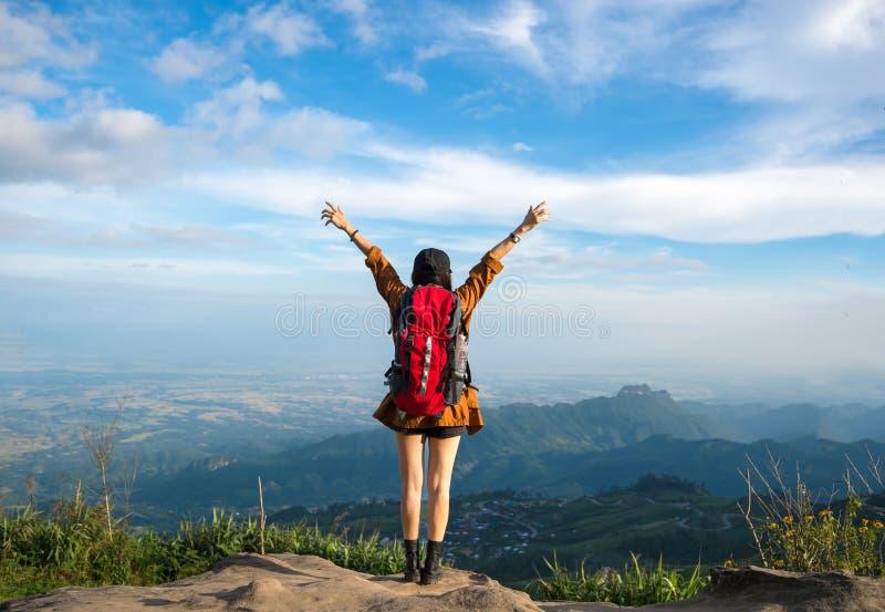 Mujer del caminante que siente el revestimiento victorioso en la montaña imagen de archivo libre de regalías
