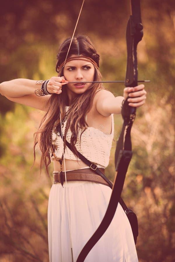 Mujer del cazador del arbolado con el arco y la flecha imagen de archivo