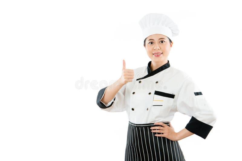 Mujer del cocinero con los pulgares felices para arriba imagen de archivo