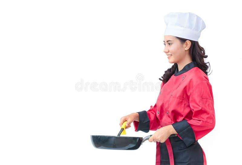 Mujer del cocinero en utensilios de cocinar que se sostienen uniformes del rojo imagenes de archivo
