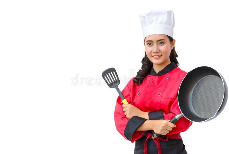 Mujer del cocinero en utensilios de cocinar que se sostienen uniformes del rojo fotos de archivo libres de regalías