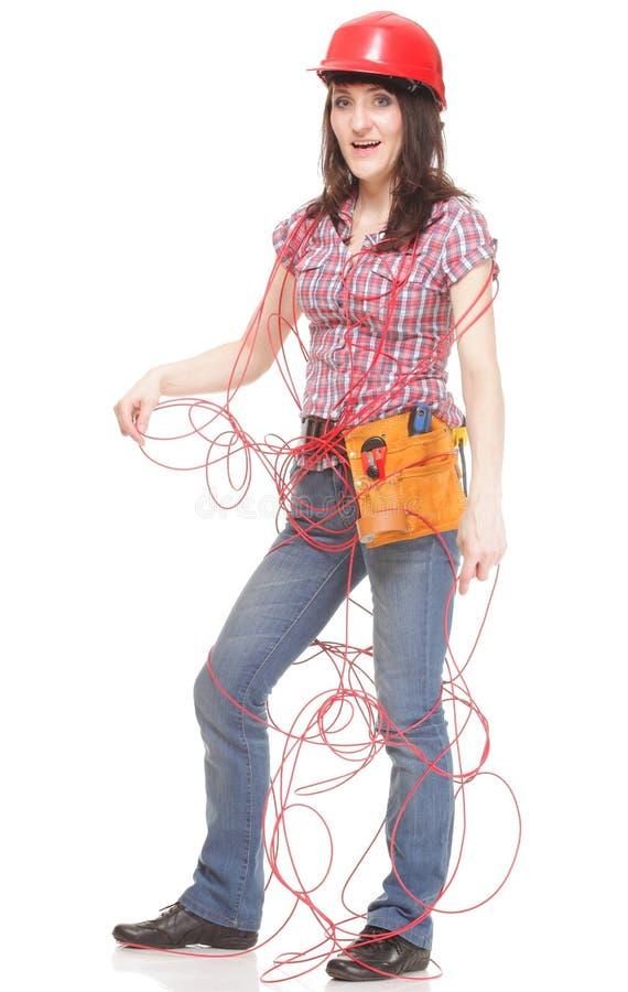 Mujer del constructor con el cable rojo enredado imagen de archivo