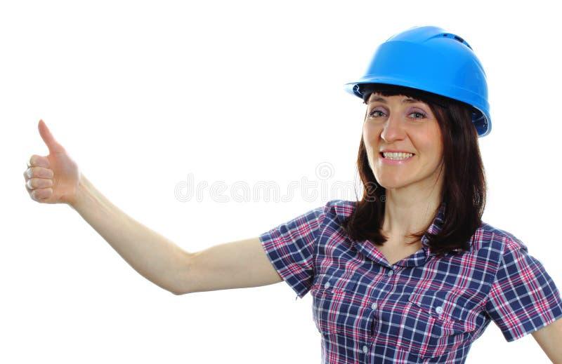 Mujer del constructor en el casco azul que muestra los pulgares para arriba foto de archivo libre de regalías