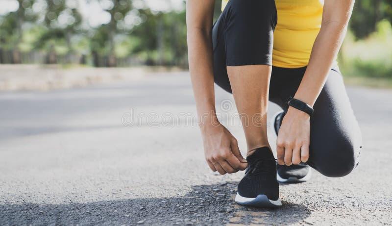 Mujer del corredor de las zapatillas deportivas que ata los cordones para el funcionamiento del otoño en Forest Park Zapatillas d foto de archivo