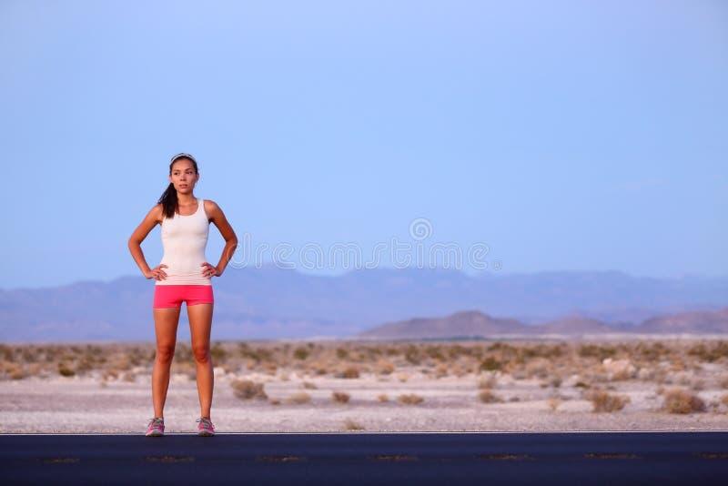 Mujer del corredor del atleta que descansa sobre el camino después de correr fotos de archivo libres de regalías
