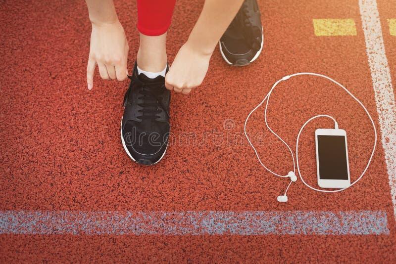 Mujer del corredor que ata cordones de zapatillas deportivas fotografía de archivo