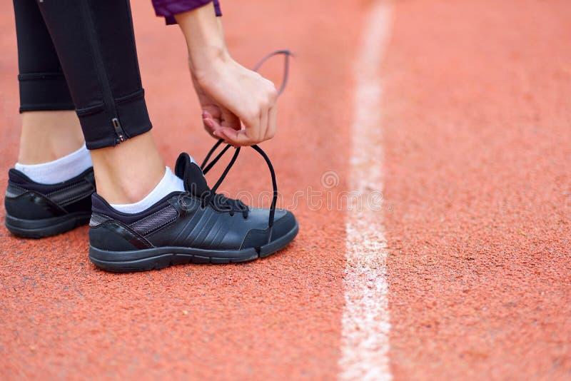 Mujer del corredor que ata los cordones de zapatillas deportivas que consiguen listos para la raza en estadio corrido de la pista foto de archivo