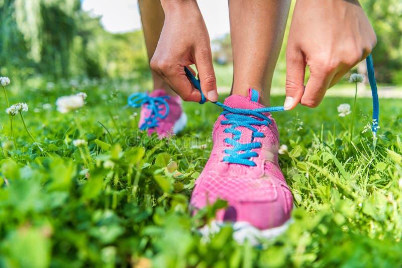Mujer del corredor que consigue las zapatillas deportivas que atan listas imagen de archivo