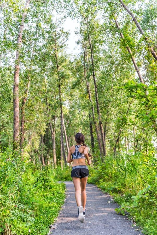 Mujer del corredor que corre en la trayectoria de la naturaleza del bosque del verano foto de archivo