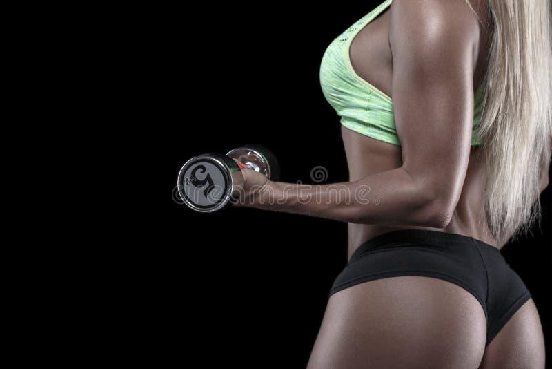 Mujer del culturista que lleva a cabo la pesa de gimnasia de plata aislada imagen de archivo libre de regalías