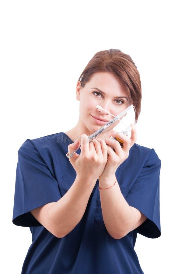 Mujer del dentista que sostiene la jeringuilla y el anestésico foto de archivo