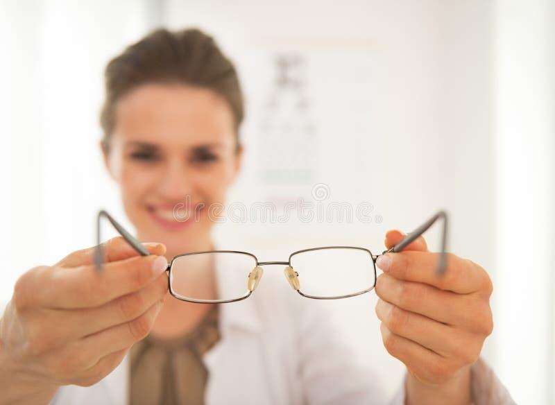 Mujer del doctor del oftalmólogo que da las lentes imagen de archivo libre de regalías
