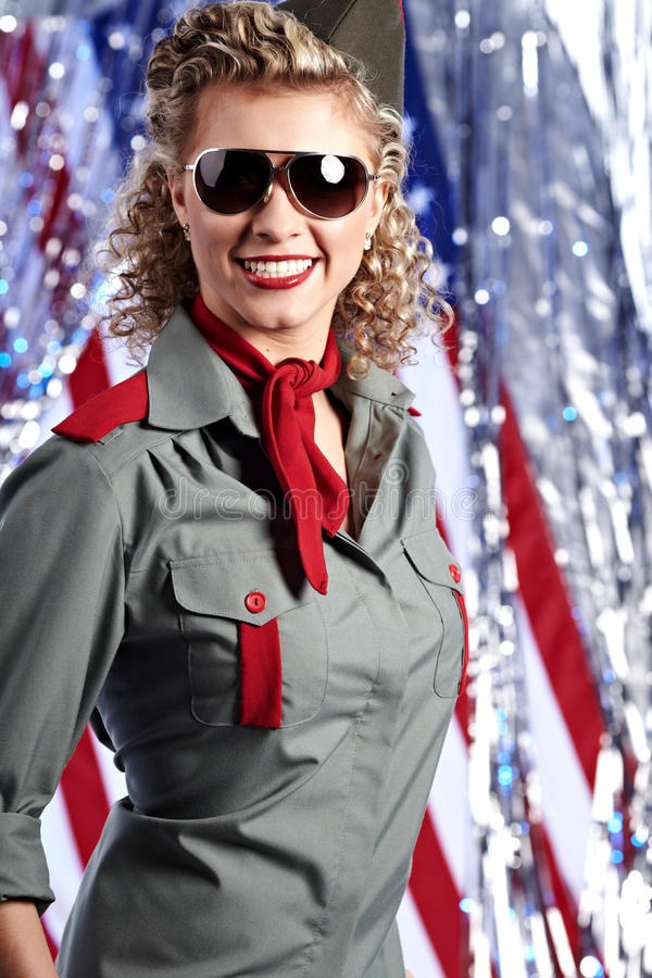 Mujer del ejército Pin-para arriba que se coloca cerca del indicador americano fotografía de archivo libre de regalías