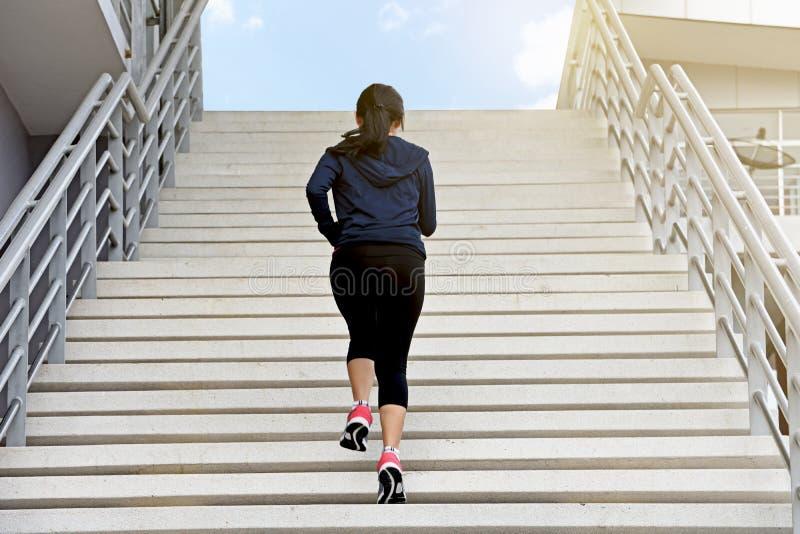 Mujer del ejercicio que corre solamente encima de las escaleras imagen de archivo