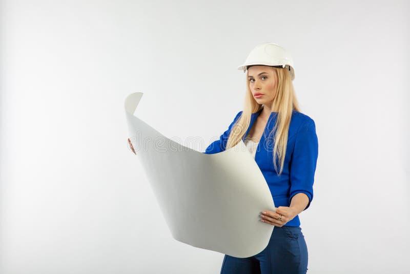 Mujer del empleado en el traje que se coloca en casco con los documentos de papel fotos de archivo