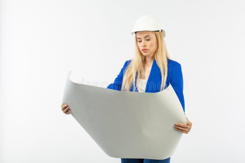 Mujer del empleado en el traje que se coloca en casco con los documentos de papel foto de archivo