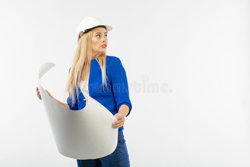 Mujer del empleado en el traje que se coloca en casco con los documentos de papel fotografía de archivo