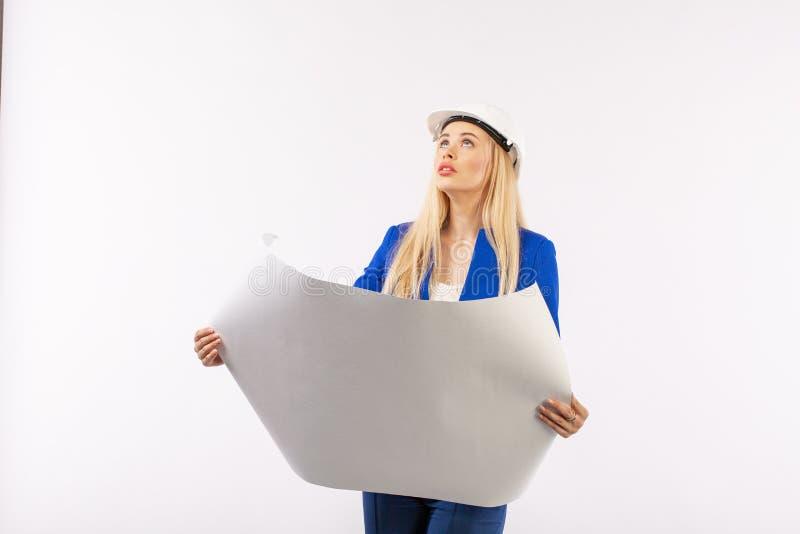 Mujer del empleado en el traje que se coloca en casco con los documentos de papel imágenes de archivo libres de regalías