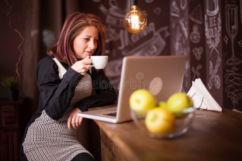 Mujer del empresario que goza de su café delante de su ordenador portátil fotos de archivo libres de regalías