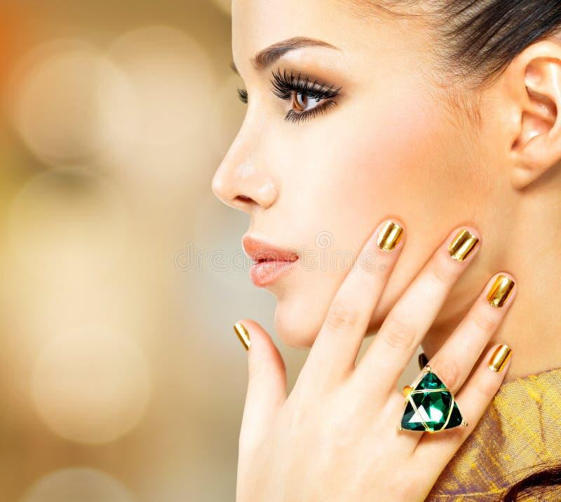 Mujer del encanto con los clavos de oro hermosos y el anillo esmeralda fotografía de archivo