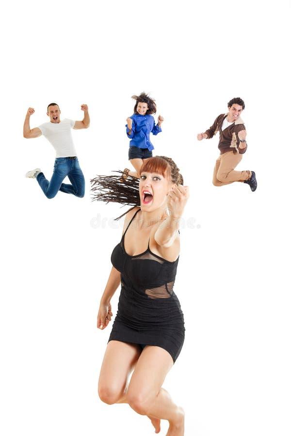 Mujer del encanto en el vestido o la muchacha oscuro que salta con el puño para arriba de la alegría fotos de archivo libres de regalías