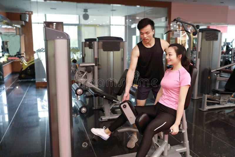 Mujer del entrenamiento del ejercicio de la extensión de la pierna del gimnasio interior Hermoso, prensa fotos de archivo libres de regalías