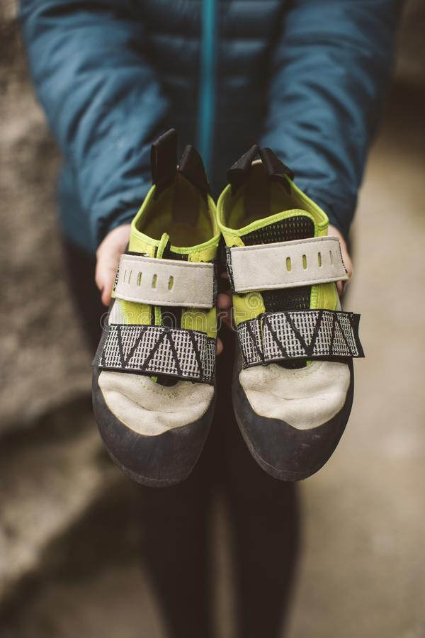 Mujer del escalador con sus zapatos que suben colocados en sus manos fotos de archivo libres de regalías
