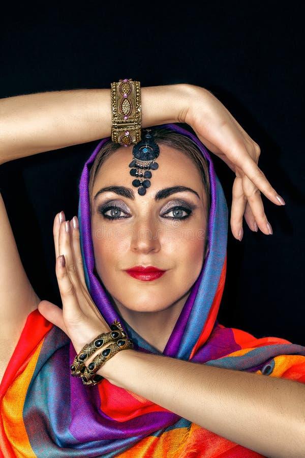 Mujer del este en burqa con las joyas en un fondo negro fotos de archivo