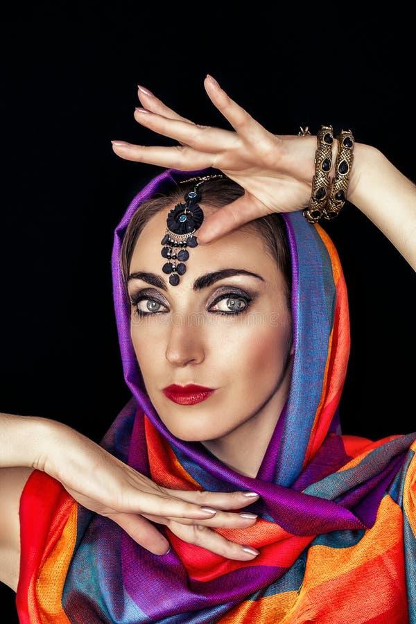 Mujer del este en burqa con las joyas en un fondo negro fotografía de archivo