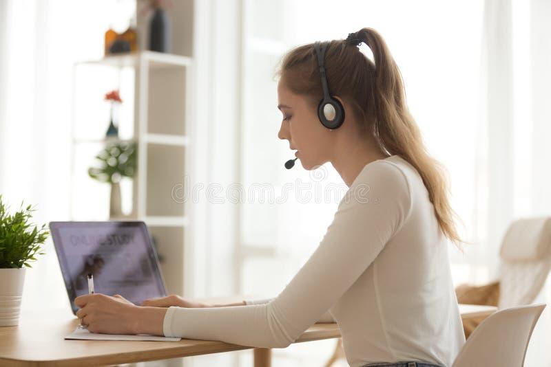 Mujer del estudiante en notas de la escritura de las auriculares, usando el ordenador portátil en el lugar de trabajo imagen de archivo libre de regalías