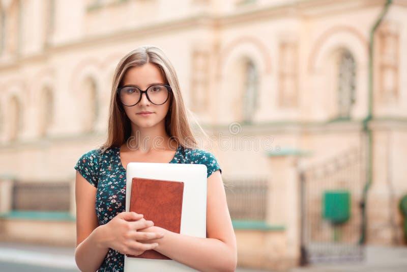 Mujer del estudiante que sostiene el ordenador port?til de la PC de los libros que parece confiado fotografía de archivo