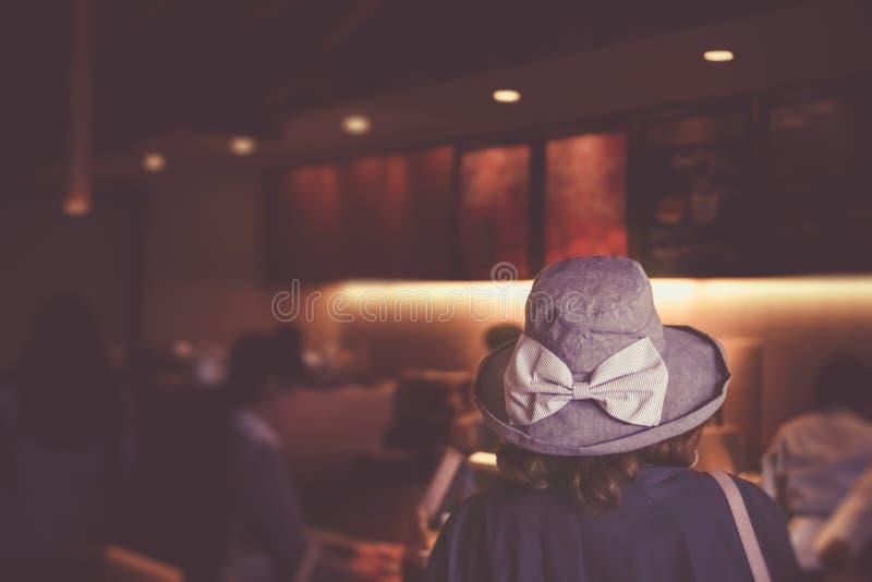 Mujer del foco selectivo que espera en línea para pedir el café en el café foto de archivo