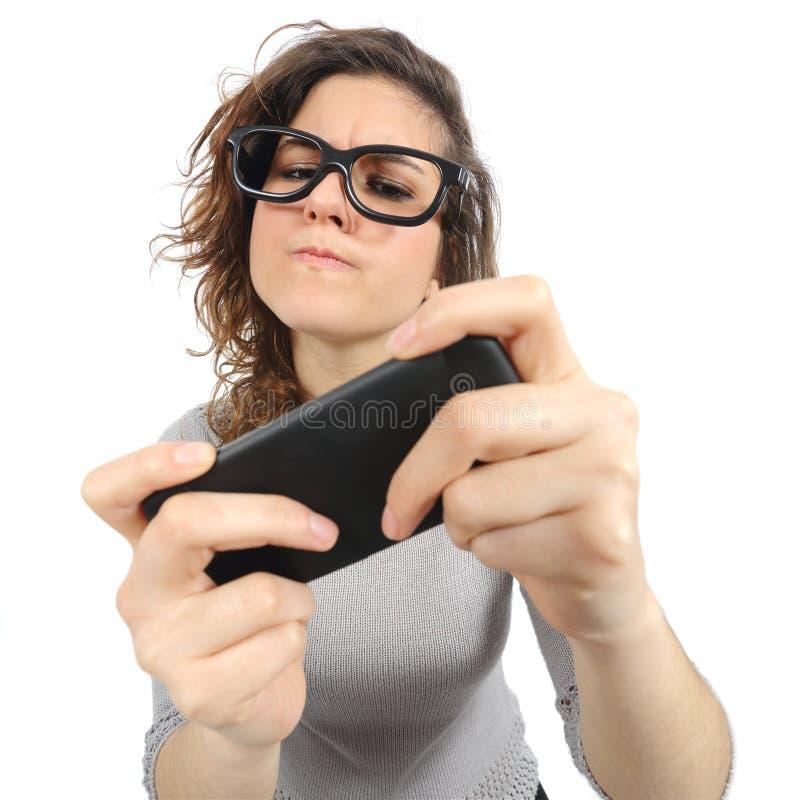 Mujer del friki que juega con un teléfono elegante foto de archivo libre de regalías